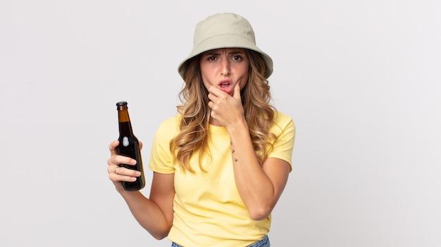 Mulher muito magra, com a boca e os olhos bem abertos e a mão no queixo, segurando uma cerveja. conceito de verão