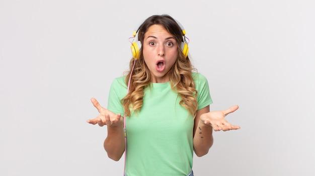 Mulher muito magra espantada, chocada e atônita com uma surpresa incrível ouvindo música com fones de ouvido