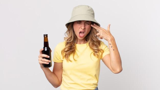 Mulher muito magra olhando infeliz e estressada, gesto de suicídio fazendo sinal de arma e segurando uma cerveja. conceito de verão