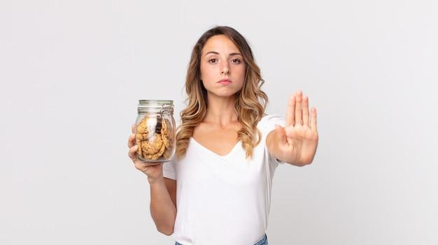 Mulher muito magra olhando séria, mostrando a palma da mão aberta, fazendo gesto de pare e segurando uma garrafa de vidro de biscoitos