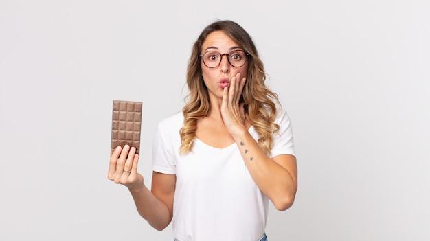 Mulher muito magra se sentindo chocada e assustada segurando uma barra de chocolate