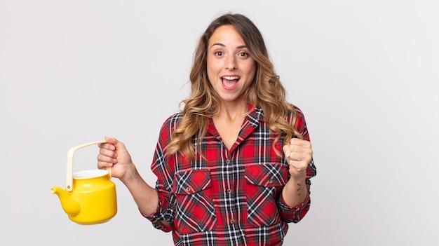 Mulher muito magra se sentindo chocada, rindo e comemorando o sucesso e segurando um bule de chá
