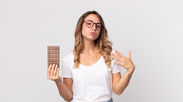 Mulher muito magra se sentindo estressada, ansiosa, cansada e frustrada segurando uma barra de chocolate