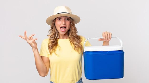 Mulher muito magra se sentindo feliz, surpresa ao perceber uma solução ou ideia e segurando uma geladeira de piquenique de verão