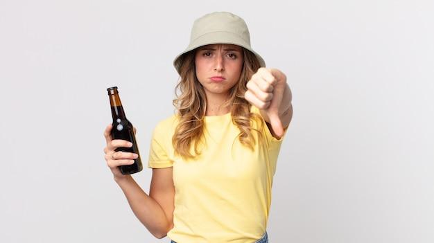 Mulher muito magra se sentindo mal, mostrando os polegares para baixo e segurando uma cerveja. conceito de verão