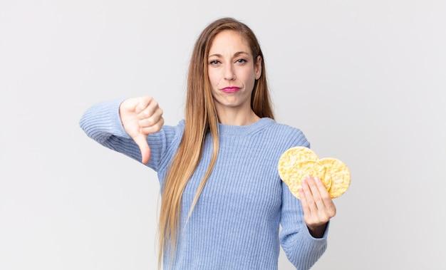 Mulher muito magra segurando um bolo de dieta de arroz