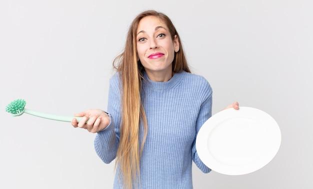 Mulher muito magra segurando um prato vazio e limpo