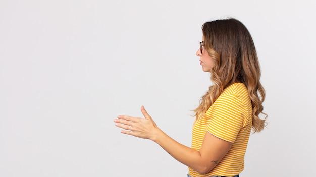 Mulher muito magra sorrindo, cumprimentando você e oferecendo um aperto de mão para fechar um negócio de sucesso, conceito de cooperação