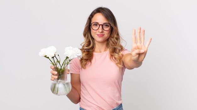 Mulher muito magra sorrindo e parecendo amigável, mostrando o número quatro e segurando flores decorativas