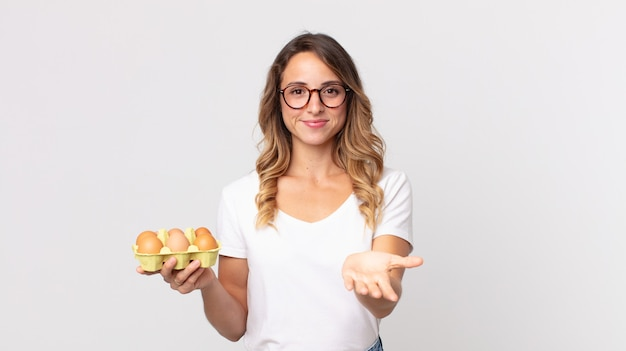 Mulher muito magra sorrindo feliz com simpatia e oferecendo e mostrando um conceito e segurando uma caixa de ovos