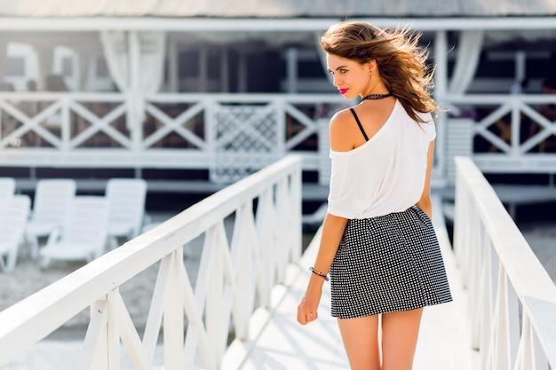 Mulher muito magro elegante com roupa de verão na moda posando perto de resort de luxo perto da praia. vestindo camisa elegante saia alta e camiseta branca.