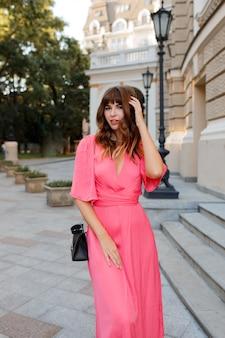 Mulher muito romântica em vestido rosa posando ao ar livre na velha europa.