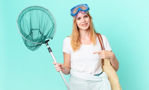 Mulher muito ruiva com uma rede de pesca e óculos de proteção.