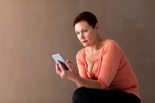 Mulher muito sênior, verificando o smartphone