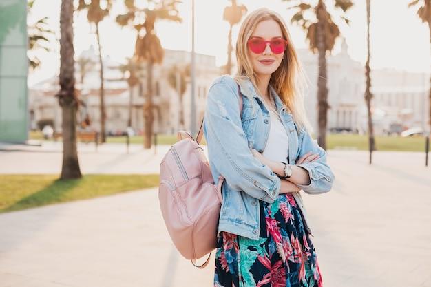 Mulher muito sorridente andando na rua da cidade com saia estampada elegante e jaqueta jeans grande e óculos de sol rosa, tendência do estilo verão
