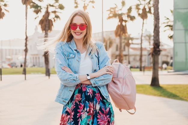 Mulher muito sorridente andando na rua da cidade com saia estampada elegante e jaqueta jeans grande e óculos de sol rosa