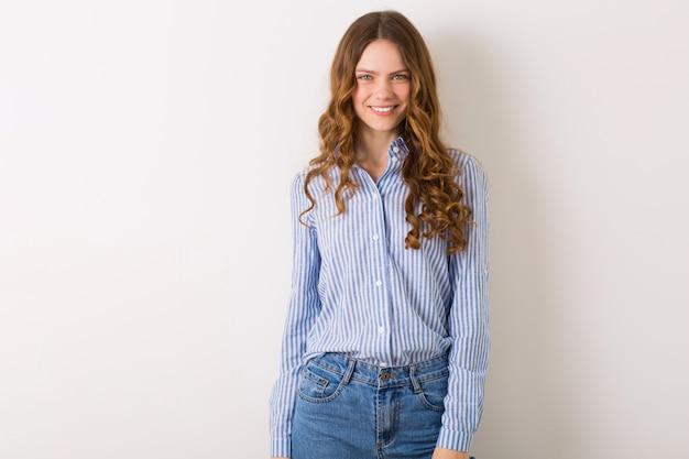 Mulher muito sorridente com roupa de verão adolescente posando contra uma parede branca