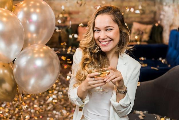 Mulher muito sorridente com um copo de uísque