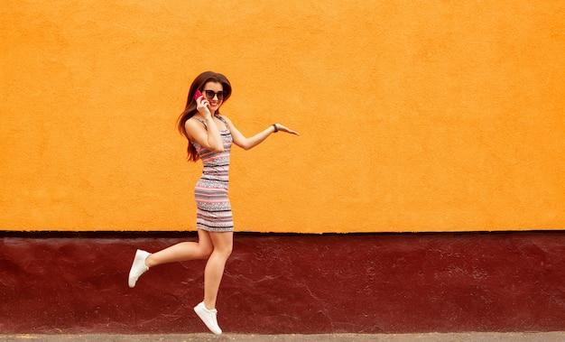 Mulher muito sorridente em óculos de sol falando no smartphone contra a parede laranja