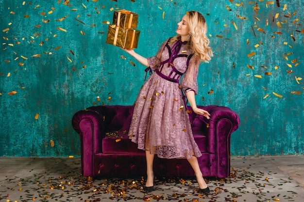 Mulher muito sorridente em um elegante vestido de noite violeta contra um sofá de veludo com presentes
