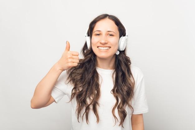 Mulher muito sorridente está ouvindo um livro de áudio, podcast ou música através de fones de ouvido e mostrando o polegar.