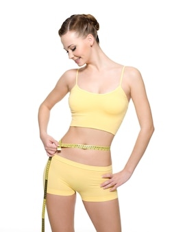 Mulher muito sorridente medindo a cintura com o tipo de medição isolado no branco