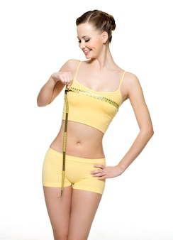 Mulher muito sorridente medindo seios com tipo de medição - isolado no branco