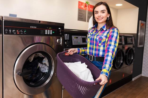 Mulher muito sorridente na lavanderia segura uma cesta de roupas.