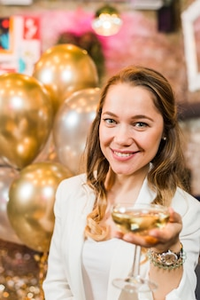 Mulher muito sorridente, oferecendo um copo de uísque