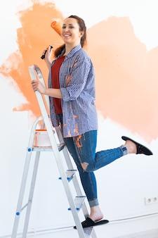 Mulher muito sorridente pintando a parede interior da casa com rolo de pintura