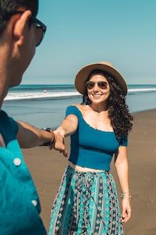 Mulher muito sorridente, puxando o homem para a praia