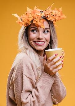Mulher muito sorridente, segurando a xícara de café e olhando para longe