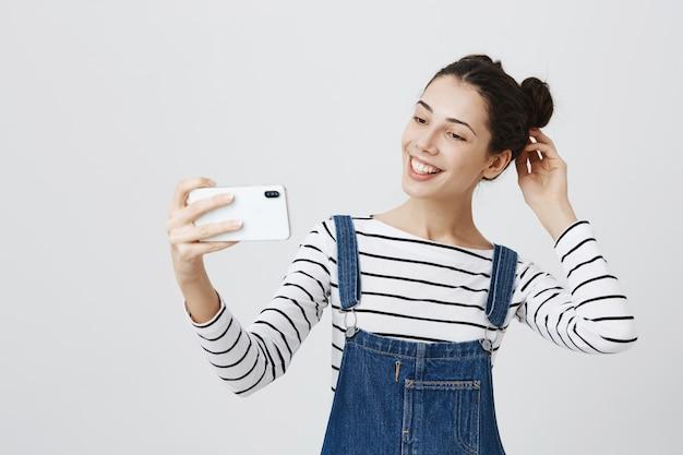 Mulher muito sorridente tirando selfie no smartphone