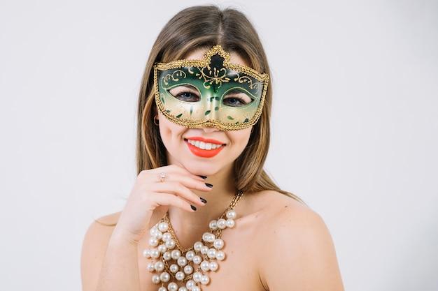 Mulher muito sorridente, vestindo a máscara decorativa de carnaval verde