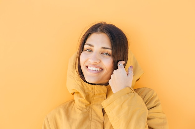 Mulher muito sorridente, vestindo jaqueta amarela com capuz, olhando para a câmera