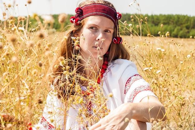 Mulher muito ucraniana vestida em roupas bordadas no campo