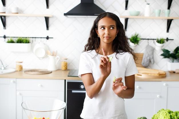 Mulher mulata bonita consciente está segurando fatias de limão na cozinha moderna, vestida com camiseta branca