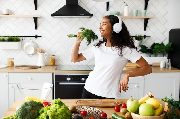 Mulher mulata bonita em fones de ouvido grandes está sorrindo e fingindo que está cantando na vegetação perto da mesa com frutas e legumes frescos