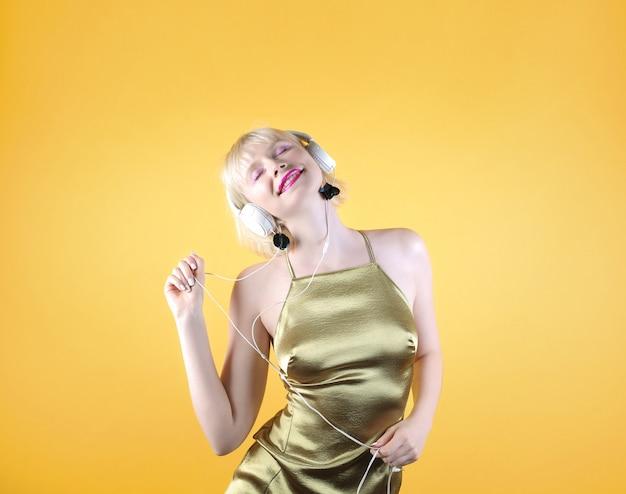 Mulher mulher bonita dançando enquanto ouve música com fones de ouvido, vestindo um vestido de noite