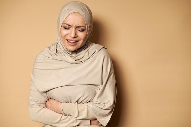 Mulher mulher usando hijab com dor de estômago.