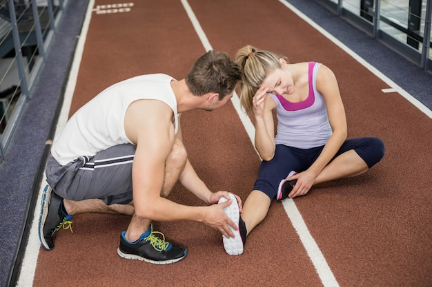 Mulher muscular com uma lesão no tornozelo no ginásio crossfit