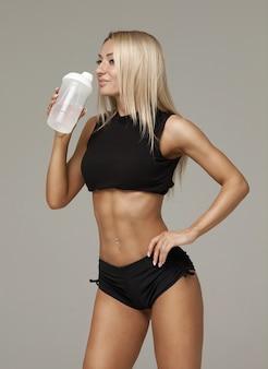 Mulher muscular desportivo água potável, isolada contra um fundo cinza