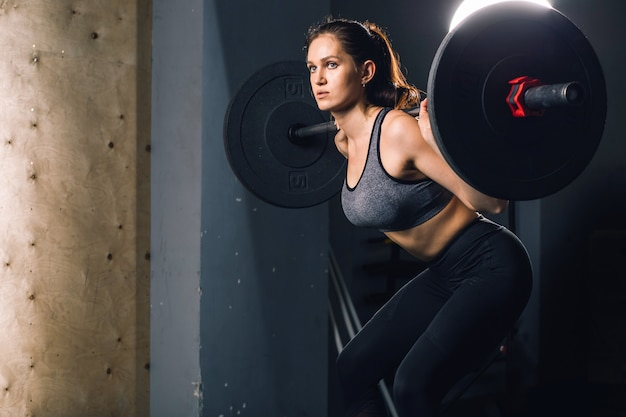 Mulher muscular em uma academia, fazendo exercícios de peso pesado com barra