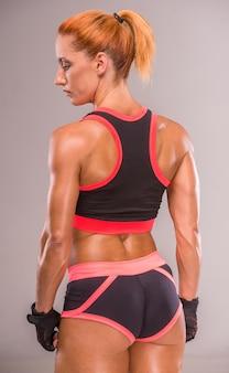 Mulher muscular está de pé