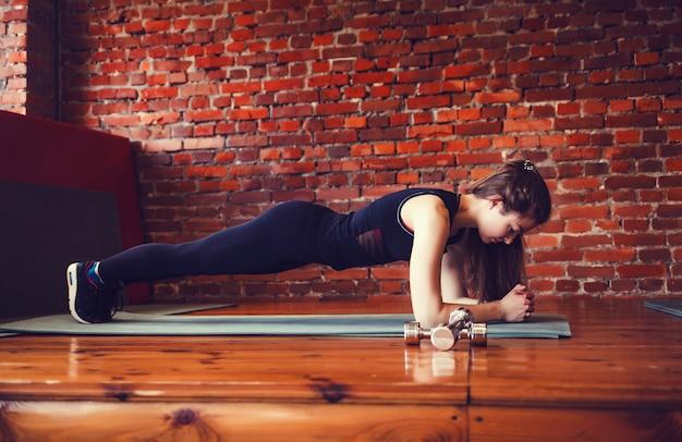 Mulher muscular fazendo exercício do núcleo