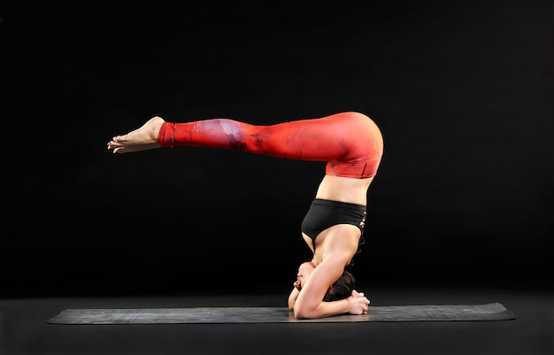 Mulher muscular fazendo um headstand com pernas de pique