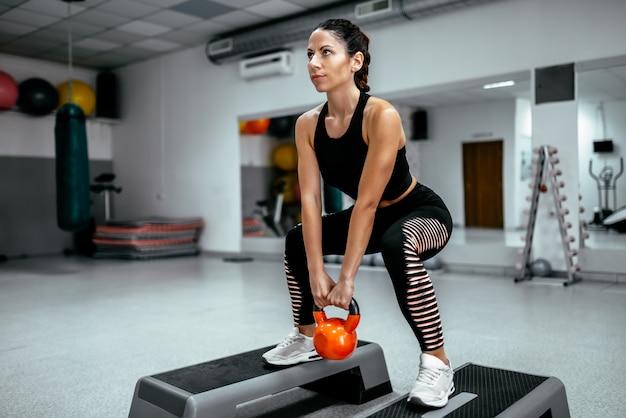 Mulher muscular que faz o exercício do crossfit na ginástica.