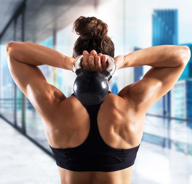 Mulher musculosa atrás de trens com kettlebell