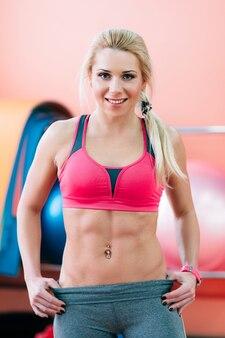 Mulher musculosa e sorridente fitness no ginásio
