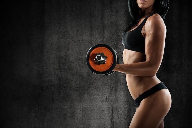 Mulher musculosa está treinando com halteres de peso